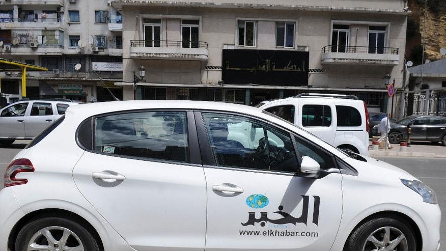 FILE - A car belonging to the Al Khabar newspaper parks outside a commercial court  in Algiers, Tuesday May 3, 2016.  Independent-minded Algerian newspaper Al Khabar is facing likely closure Wednesday May 4, 2016, after the government cracked down on its advertising and challenged its pending sale in commercial court. The newspaper has been critical of the government, notably its handling of the gas-dependent economy. (AP Photo/Sidali Djarboub)