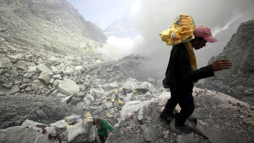 In this April 16, 2016 photo, a miner tries to balance his steps as he carries sulfur slabs on his shoulders up from the crater of Mount Ijen in Banyuwangi, East Java, Indonesia. Stunning Mount Ijen in east Java draws tourists by day and hundreds of sulfur miners by night. More than 9,000 feet above sea level, the men descend into the volcano's crater to dig out slabs of bright yellow sulfur, enduring toxic fumes and back-breaking loads to earn $10 a day delivering a substance used to bleach sugar and vulcanize rubber. (AP Photo/Binsar Bakkara)