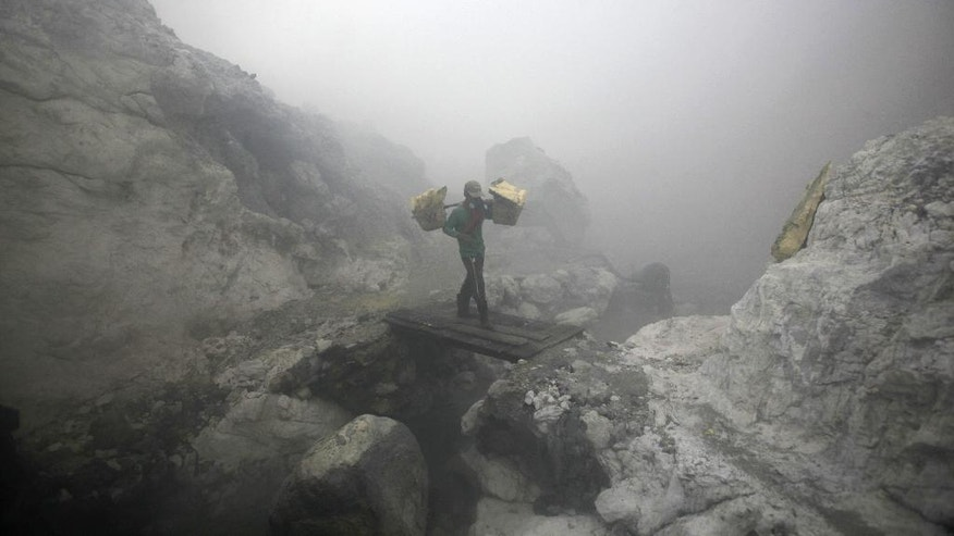In this April 16, 2016 photo, a sulfur miner carries baskets full of sulfur slabs through volcanic smoke as he climbs up from the crater of Mount Ijen in Banyuwangi, East Java, Indonesia. Stunning Mount Ijen in east Java draws tourists by day and hundreds of sulfur miners by night. More than 9,000 feet above sea level, the men descend into the volcano's crater to dig out slabs of bright yellow sulfur, enduring toxic fumes and back-breaking loads to earn $10 a day delivering a substance used to bleach sugar and vulcanize rubber. (AP Photo/Binsar Bakkara)