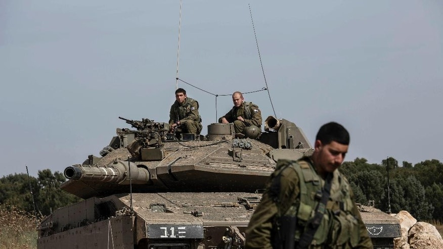 Israeli soldiers sit on a tank near the Israel Gaza border, Wednesday, May 4, 2016. The Israeli army says a tank has fired at a target in the northern Gaza Strip following an explosion on the Palestinian side of the border. The army says it's trying to determine the source of the explosion, which took place on Wednesday. Earlier, a tank fired into Gaza after a mortar shell was launched toward Israeli forces near the southern Gaza Strip. (AP photo/Tsafrir Abayov)
