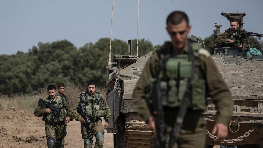 Israeli soldiers walk by a tank near the Israel Gaza border, Wednesday, May 4, 2016. The Israeli army says a tank has fired at a target in the northern Gaza Strip following an explosion on the Palestinian side of the border. The army says it's trying to determine the source of the explosion, which took place on Wednesday. Earlier, a tank fired into Gaza after a mortar shell was launched toward Israeli forces near the southern Gaza Strip. (AP photo/Tsafrir Abayov)