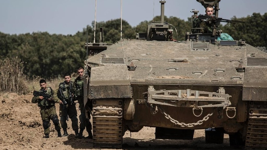 Israeli soldiers stand by a tank near the Israel Gaza border, Wednesday, May 4, 2016. The Israeli army says a tank has fired at a target in the northern Gaza Strip following an explosion on the Palestinian side of the border. The army says it's trying to determine the source of the explosion, which took place on Wednesday. Earlier, a tank fired into Gaza after a mortar shell was launched toward Israeli forces near the southern Gaza Strip. (AP photo/Tsafrir Abayov)