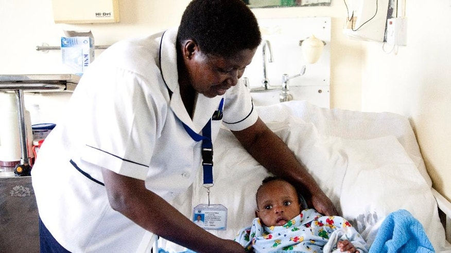 A nurse at Kenyatta National Hospital attends to Dealeryn Saisi Wasike, the nearly 6-month-old girl who was rescued early Tuesday from the rubble of a building that collapsed last week, lies in a hospital bed at Kenyatta National Hospital in Nairobi, Kenya Wednesday, May 4, 2016. The girl was brought to the hospital after being found in the ruins of the seven-story building that collapsed Friday night but had no physical injuries and was being treated for dehydration, according to a hospital spokesman. (AP Photo/Sayyid Abdul Azim)