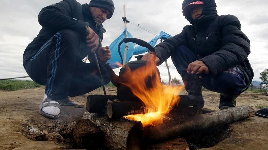 Aded Rahim, left, and Mohammed Aziz, both from Syria, stand by a fire at at the northern Greek border point of Idomeni, Greece, Wednesday, May 4, 2016. European Union countries that refuse to accept refugees under proposals to overhaul the EU's failed asylum laws could face large fines for each asylum seeker rejected. (AP Photo/Gregorio Borgia)