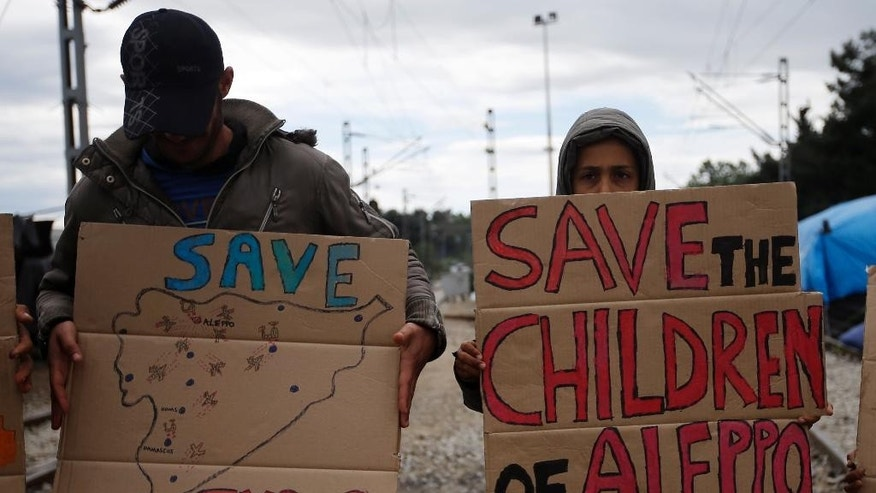Refugees from Syria holds placards during a demonstration in the northern Greek border point of Idomeni, Greece, Wednesday, May 4, 2016. European Union countries that refuse to accept refugees under proposals to overhaul the EU's failed asylum laws could face large fines for each asylum seeker rejected. (AP Photo/Gregorio Borgia)