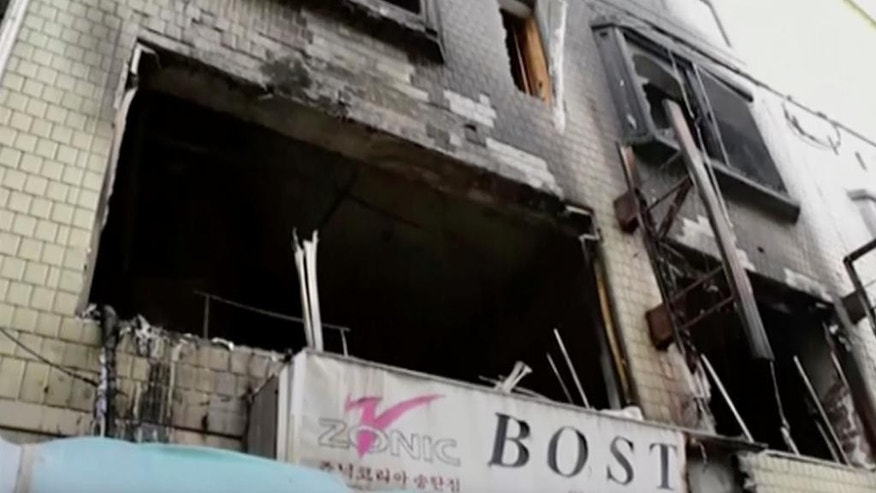 In this May 2, 2016 image, made from video provided by DVIDS, a building is burned after a fire where residents, including U.S. servicemen, used a blanket to catch a woman and her three children as they jumped to safety in Pyeongtaek, South Korea. South Korean officials say residents rescued the four from a fire by safely catching them with a blanket as they fell four floors. (DVIDS via AP)