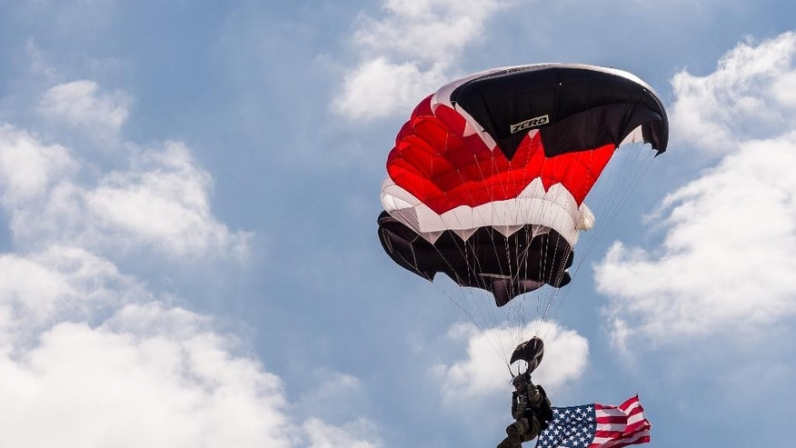 A member of the NATO parachute demonstration team lands during a change of command ceremony at NATO military headquarters in southern Belgium.