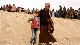 A Syrian refugee man and boy cross into Jordan at the Hadalat reception area on the Syrian-Jordanian border, about 320 kilometers (200 miles) northeast of the capital of Amman, Wednesday, May 4, 2016. The commander of Jordan's Border Guard Forces says the number of Syrian refugees amassed in remote desert areas on the Jordanian border and waiting to enter has risen to a new high of 59,000. (AP Photo/Raad Adayleh)