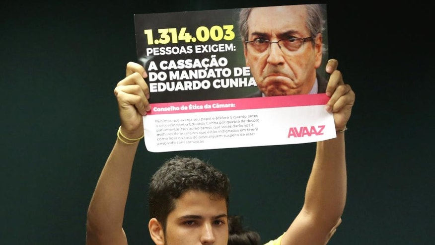 "FILE - In this April 26, 2016 file photo, a demonstrator hold a sign that reads in Portuguese ""1,314,003 people require the mandate of Eduardo Cunha be annulled"" during a protest against the president of House Speaker Eduardo Cunha, before the ethics committee of the Chamber of Deputies in Brasilia, Brazil. Cunha was named among many top officials to be investigated for corruption by the Supreme Court, authorized by Brazil's attorney general according to Brazilian news reports on Monday, May 2, 2016. (AP Photo/Eraldo Peres, File)"