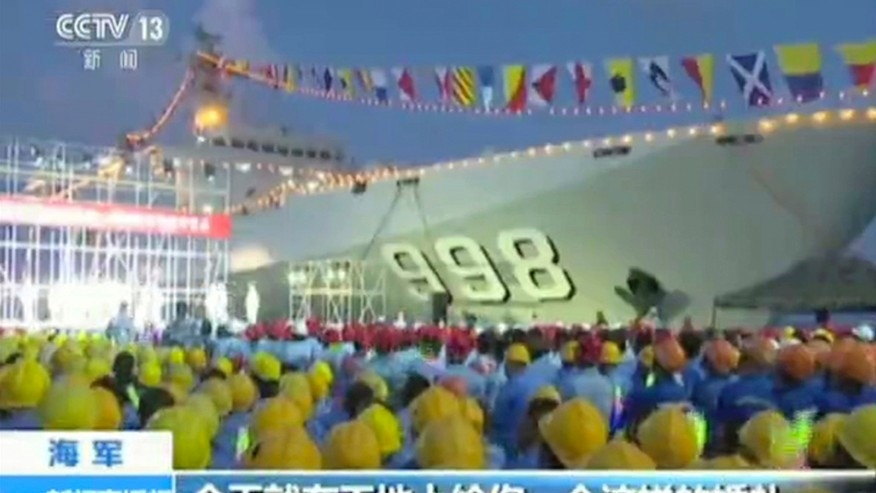 May 2, 2016: In this image taken from a video run by China's CCTV via AP Video, workers gather near a Chinese military ship during a performance for navy officers and construction workers on Fiery Cross Reef in the South China Sea