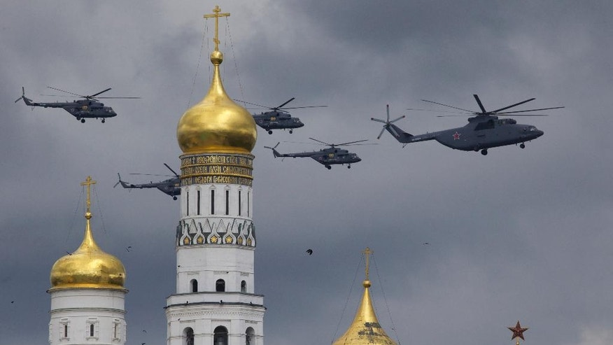 Russian military helicopters fly over Ivan the Great bell-tower and Moscow's Kremlin during a general rehearsal for the Victory Day military parade which will take place at Moscow's Red Square on May 9 to celebrate 71 years after the victory in WWII in Moscow, Russia, on Thursday, May 5, 2016. (AP Photo/Ivan Sekretarev)