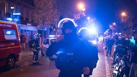 FILE- In this Friday, Nov. 13, 2015 file photo, elite police officers arrive outside the Bataclan theater after several dozen people were killed in attacks around Paris. A French Islamic State cell dismantled in the final stages of planning an attack has yielded a new secret in the first week of May 2016, with the release of undercover footage showing how a group of disaffected petty criminals transformed into a terror network. (AP Photo/Kamil Zihnioglu, File)