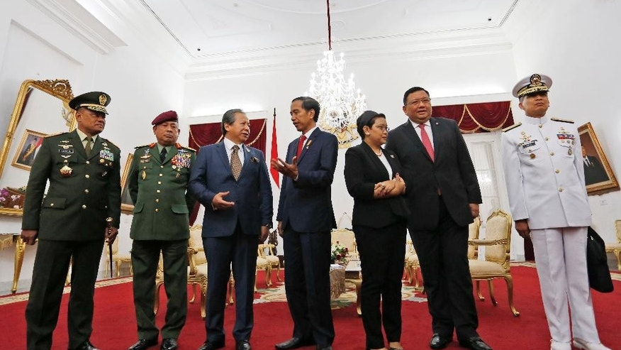 From left to right, Indonesian Armed Forces Chief Gen. Gatot Nurmantyo, his Malaysian counterpart Gen. Zulkifeli Mohd. Zin, Malaysia's Foreign Minister Anifah Aman, Indonesian President Joko Widodo, Indonesian Foreign Minister Retno Marsudi, her Filipino counterpart Foreign Minister Jose Rene Almendras, and the Philippine's Navy Chief Rear Adm. Caesar C. Taccad, confer as they prepare for a group photo before the start of their trilateral meeting on maritime security issues at the presidential palace in Yogyakarta, Indonesia, Thursday, May 5, 2016. The gathering was held following the kidnappings of Indonesian and Malaysian crewmen by Abu Sayyaf militants in the waters off southern Philippines where Indonesia share borders with the two countries. (AP Photo/Rana Dyandra)