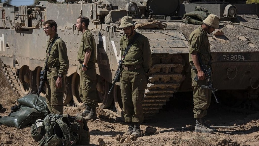 Israeli soldiers stand in silence as sirens wailed across Israel for two minutes marking the annual Day of Remembrance for victims of the Holocaust, near the Israel Gaza border, Thursday, May 5, 2016. (AP photo/Tsafrir Abayov)