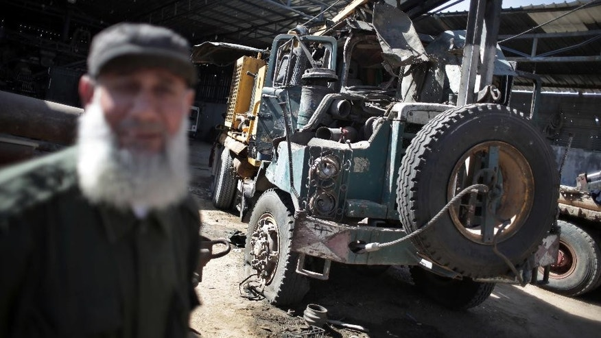 A Palestinian man inspects a damaged artesian well drilling truck after an early morning Israeli airstrike hit a workshop in Gaza City, Thursday, May 5, 2016. (AP Photo/ Khalil Hamra)