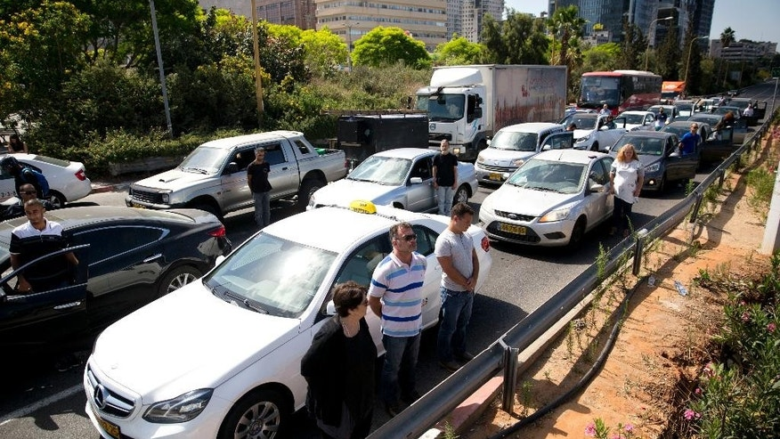 Israelis stand still next to their cars as a siren sounds in memory of victims of the Holocaust, in Tel Aviv.