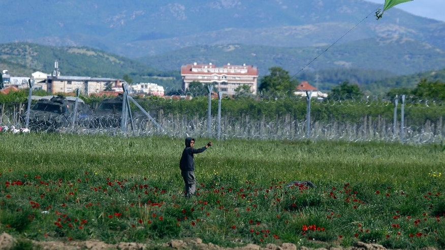 A child flies a kite near a fence at the northern Greek border point of Idomeni, Greece, Thursday, May 5, 2016. The European Union pressed ahead Wednesday with efforts to persuade Turkey to stop asylum seekers from reaching Europe and take back thousands more by offering Turkish citizens the prospect of visa-free travel within the bloc. (AP Photo/Gregorio Borgia)