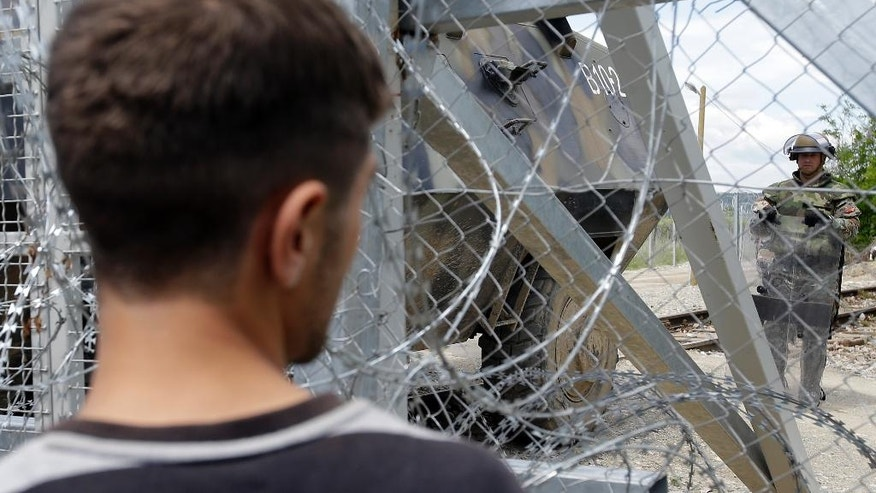 A man looks a t a Macedonian soldier during a protest at the northern Greek border point of Idomeni, Greece, Thursday, May 5, 2016. Migrants and refugees protested against the poor camp conditions and the closed border. (AP Photo/Gregorio Borgia)