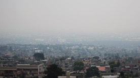Air pollution hangs over Mexico City, Tuesday, May 3, 2016. Mexico City authorities have declared a new pollution alert and will require 40 percent of cars to keep off the streets. (AP Photo/Eduardo Verdugo)
