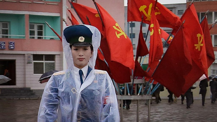 A North Korean traffic police woman directs vehicles at a street junction while behind her the sidewalk is decorated with flags of the ruling party, the Workers' Party on Thursday, May 5, 2016, in Pyongyang, North Korea. Members of North Korea's ruling party have gathered in Pyongyang ahead of their biggest political conference in decades. Foreign experts say North Korea's leader Kim Jong Un will likely use the meeting to place his loyalists into key positions, strengthen his push to upgrade his country's nuclear arsenal and cement his grip on power. (AP Photo/Wong Maye-E)