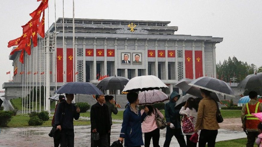 North Koreans carry umbrellas as they walk past the April 25 House of Culture, decorated in the colors and flags of their ruling party, the Workers' Party on Thursday, May 5, 2016, in Pyongyang, North Korea. Members of North Korea's ruling party have gathered in Pyongyang ahead of their biggest political conference in decades. Foreign experts say North Korea's leader Kim Jong Un will likely use the meeting to place his loyalists into key positions, strengthen his push to upgrade his country's nuclear arsenal and cement his grip on power. (AP Photo/Wong Maye-E)