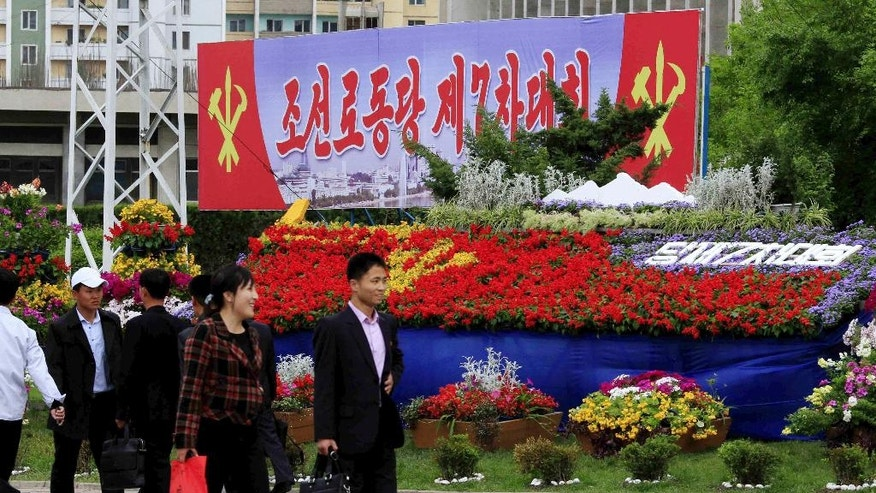 "Pedestrians walk by a flower arrangement and billboard with the words ""The 7th Congress of the Workers' Party of Korea"" Thursday, May 5, 2016, in Pyongyang, North Korea. Members of North Korea's ruling party have gathered in Pyongyang ahead of their biggest political conference in decades. Foreign experts say North Korea's leader Kim Jong Un will likely use the meeting to place his loyalists into key positions, strengthen his push to upgrade his country's nuclear arsenal and cement his grip on power. (AP Photo/Kim Kwang Hyon)"