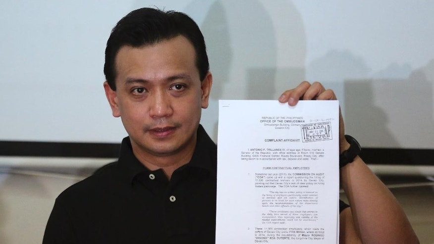 Philippine senator and vice presidential candidate Senator Antonio Trillanes IV shows a document during a press conference in suburban Quezon city, north of Manila, Philippines on Thursday, May 5, 2016. Senator Trillanes has filed a corruption complaint against the presidential race front runner Davao City Mayor Rodrigo Duterte alleging he charged salaries for 11,000 non-existent government employees. (AP Photo/Aaron Favila)
