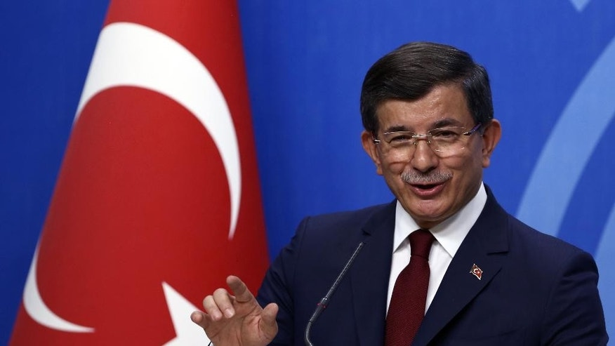 Turkish Prime Minister Ahmet Davutoglu smiles as he speaks to the media at the headquarters of his ruling Justice and Development Party, AKP, in Ankara, Turkey, Thursday, May 5, 2016. Davutoglu announced his resignation on Thursday, paving the way for the country's president to pursue a tighter grip on power. Davutoglu, who had fallen out with President Recep Tayyip Erdogan, announced he was stepping aside following a meeting with executives of the AKP.(AP Photo/Burhan Ozbilici)