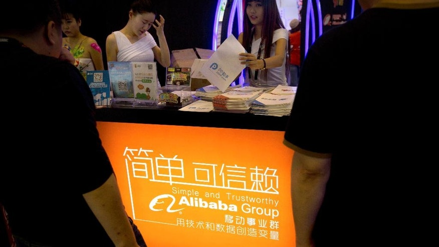 In this April 29, 2015 photo, staff members hand out brochures to visitors at the Alibaba Group's booth at the Global Mobile Internet Conference in Beijing. The International Anti-Counterfeiting Coalition's decision to welcome Chinese e-commerce giant Alibaba as a new member - and allow founder Jack Ma to make the keynote speech at its May 2016 conference - so incensed the U.S. luxury retailer Michael Kors that it severed its longstanding connection with the Washington-based industry group. (AP Photo/Mark Schiefelbein)