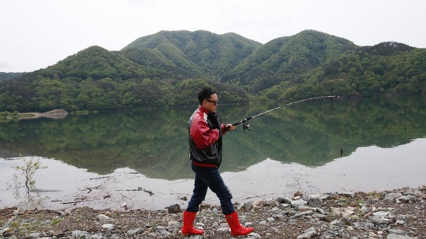 "In this April 28, 2016 photo, South Korean Koo Eun-je, the 35-year-old host of the Cat TV, walks along a lake to try to catch fish for street cats in Jangseong, South Korea. The stars of the latest online trend in South Korea are stray cats, eating food left out for them as viewers sit enrapt at their feline charms. Koo's livestreamed ""Cats Meok Bang"" show is a twist on an online trend of young South Korean men and women tucking into feasts in real time, while viewers send messages and sometimes virtual cash. (AP Photo/Lee Jin-man)"