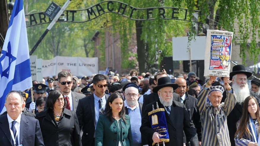 "Rabbi Yisrael Meir Lau, fourth right, and Israeli Minister of Justice Ayelet Shaked, sixth right, walk through the gate with the inscription ""Arbeit Macht Frei"" (work sets you free) in the Auschwitz-Birkenau German Nazi Death Camp at the start of the yearly March of the Living, in Oswiecim, Poland, Thursday, May 5, 2016. (AP Photo/Alik Keplicz)"