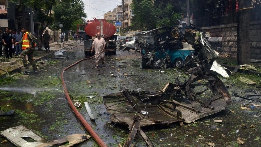"In this photo released by the Syrian official news agency SANA, Syrian citizens and firefighters gather at the scene where one of rockets hit the Dubeet hospital in the central neighborhood of Muhafaza in Aleppo, Syria, Tuesday, May 3, 2016. Shells and mortar rounds are raining down on every neighborhood Aleppo,"" said Aleppo-based health official Mohammad Hazouri, speaking from Al-Razi hospital.  (SANA via AP)"