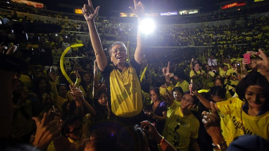 "FILE - In this April 28, 2016, file photo, Philippine Presidential candidate Mar Roxas, center, former Interior and local Government secretary, flashes the ""L"" sign for ""Laban"" meaning Fight! during a campaign sortie in suburban Quezon city, north of Manila, Philippines. A U.S.-educated investment banker and the richest Philippine presidential aspirant, Roxas lacks the dramatic life stories of his rivals, including a tough-talking mayor with a public vow to dump criminals in Manila Bay and a foundling who made it big in politics. (AP Photo/Aaron Favila, File)"