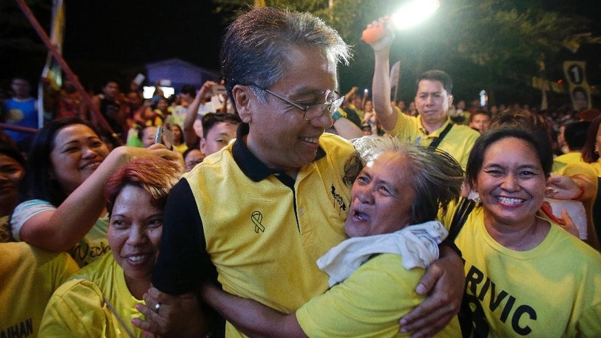 FILE - In this April 28, 2016, file photo, Philippine presidential candidate Mar Roxas, center,former Interior and local government secretary, hugs a supporter during a campaign sortie in suburban Quezon city, north of Manila, Philippines. A U.S.-educated investment banker and the richest Philippine presidential aspirant, Roxas lacks the dramatic life stories of his rivals, including a tough-talking mayor with a public vow to dump criminals in Manila Bay and a foundling who made it big in politics. (AP Photo/Aaron Favila, File)