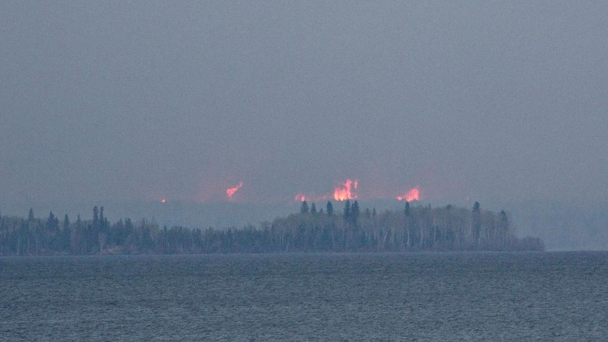 A wildfire burns across Gregoire Lake near Fort McMurray, Canada, Thursday, May 5, 2016. Canadian officials will start moving thousands of people from work camps north of devastated Fort McMurray in a mass highway convoy Friday morning if it is safe from the wildfire raging in Alberta. (Jason Franson/The Canadian Press via AP) MANDATORY CREDIT