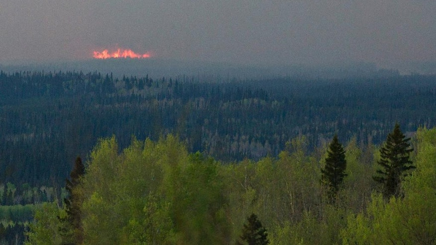 A wildfire flares up near Fort McMurray, Canada, Thursday, May 5, 2016. Canadian officials will start moving thousands of people from work camps north of devastated Fort McMurray in a mass highway convoy Friday morning if it is safe from the wildfire raging in Alberta. (Jason Franson/The Canadian Press via AP) MANDATORY CREDIT