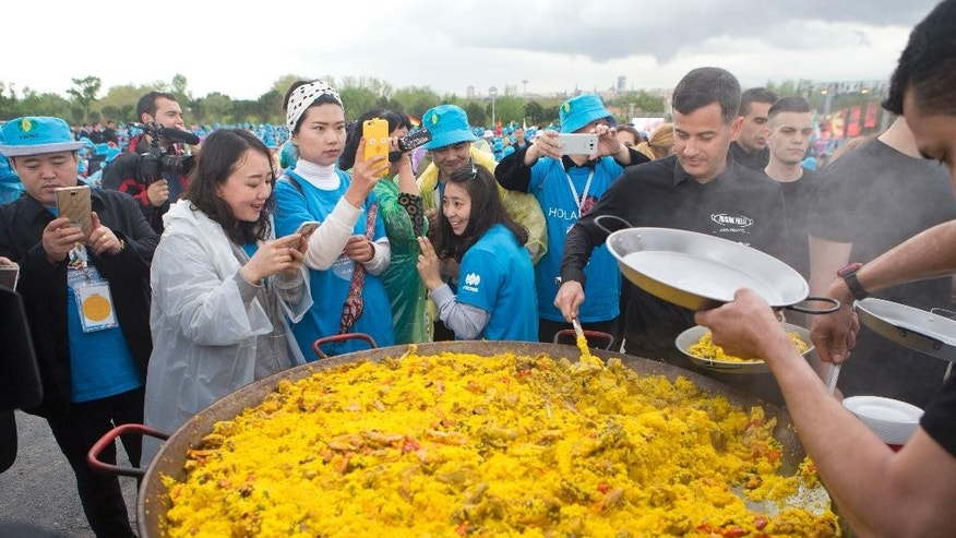 Chinese conglomerate Tiens Group employers take photos while waiting to be served Paella in Madrid, Spain, Friday, May 6, 2016. The billionaire founder of Chinese conglomerate Tiens Group is treating 3,000 of his best salespeople to a traditional Spanish paella meal in a free Madrid trip that also includes a bullfight and a tour of King Felipe VI's Royal Palace. The smiling salespeople washed down their heaping plates of paella with sangria Friday at a mass spread of picnic tables in a riverside park during the event footed by Li Jinyuan and organized by China's U Tour travel company. (AP Photo/Paul White)