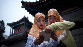 FILE - In this Aug. 1, 2011 file photo, two Chinese Hui Muslim girls read the Quran, Islam's holy book, at the Niujie Mosque as they wait for their fast on the first day of the Muslim holy month of Ramadan in Beijing. A heavily Muslim Chinese province has demanded strict adherence to a ban on religion in schools after a video circulated online in which a kindergartener recites verses from the Quran. (AP Photo/Andy Wong, File)