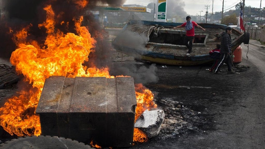 Fishermen who have lost their livelihoods due to a poisonous algae known as red tide protest with burning barricades as they demand government compensation on Chiloe Island, Chile, Friday, May 6, 2016. Some local residents blame salmon-farm owners for the red tide that has affected seven major cities and dozens of fishing towns. But experts say it's linked to high temperatures stemming from the El Nino weather pattern. (AP Photo/Esteban Felix)