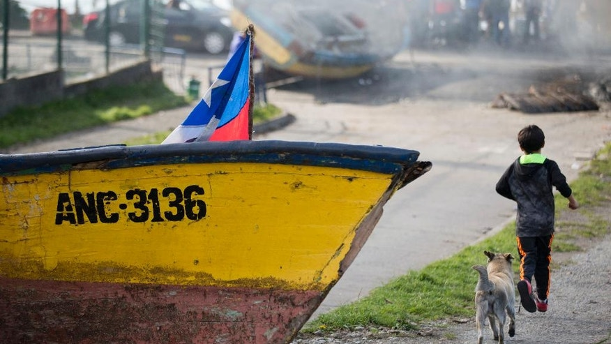 A boat blocks a road during a protest by fishermen who've lost their livelihoods due to the poisonous algae known as red tide on Chiloe Island, Chile, Friday, May 6, 2016. Some local residents blame salmon-farm owners for the red tide that has affected seven major cities and dozens of fishing towns, but experts say it's linked to high temperatures stemming from the El Nino weather pattern. (AP Photo/Esteban Felix)