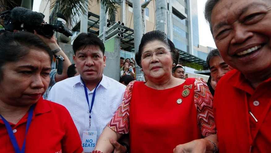"""Former First Lady and now Congresswoman Imelda Marcos, center, arrives to lend support to her son Vice-presidential candidate Sen. Ferdinand """"Bongbong"""" Marcos Jr., on his last campaign rally for Monday's presidential elections Thursday, May 5, 2016 at suburban Mandaluyong city east of Manila, Philippines. Marcos, the son of the late Philippine strongman Ferdinand Marcos, is in a """"statistical tie"""" with administration candidate Leni Robredo in poll surveys leading to May 9 elections.(AP Photo/Bullit Marquez)"""