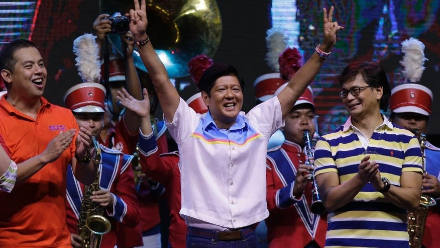 """Vice Presidential candidate Sen. Ferdinand """"Bongbong"""" Marcos Jr., center, flashes the """"V"""" sign during his last campaign rally for Monday's presidential elections Thursday, May 5, 2016 at suburban Mandaluyong city, east of Manila, Philippines. Marcos, the son of the late Philippine strongman Ferdinand Marcos, is in a """"statistical tie"""" with vice presidential candidate Leni Robredo in poll surveys leading to May 9 elections. (AP Photo/Aaron Favila)"""