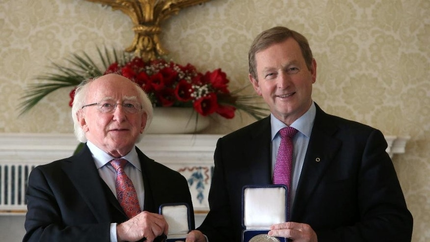 Newly elected Prime Minister Enda Kenny, right, receives the Seal of the Taoiseach and Seal of Government from President Michael D. Higgins at Aras an Uachtarain, Dublin, Friday, May 6, 2016. Prime Minister Enda Kenny won narrow re-election Friday on his fourth attempt, ending 70 days of deadlock caused by an inconclusive election and clearing the way for formation of an exceptionally fragile minority government. (Brian Lawless/PA via AP)     UNITED KINGDOM OUT        -     NO SALES       -       NO ARCHIVES