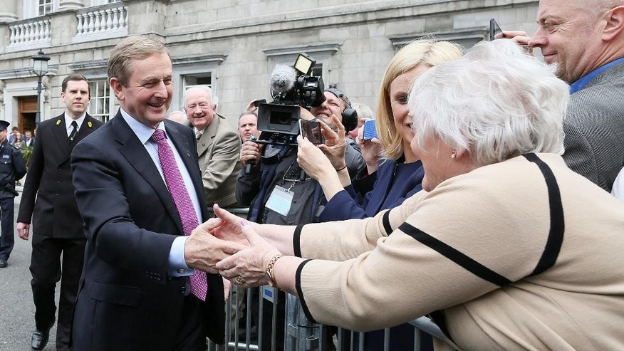 Newly elected Prime Minister Enda Kenny greets supporters as he leaves Leinster House, Dublin, to go to Aras an Uachtarain, the official residence of the President of Ireland, to receive the Seal of the Taoiseach and Seal of Government, Friday May 6, 2016. Prime Minister Enda Kenny won narrow re-election Friday on his fourth attempt, ending 70 days of deadlock caused by an inconclusive election and clearing the way for formation of an exceptionally fragile minority government. (PA via AP) UNITED KINGDOM OUT