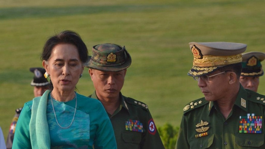 Myanmar's foreign minister and de facto leader, Aung San Suu Kyi, left, walks with Commander-in-Chief of the Myanmar Armed Forces General Min Aung Hlaing, right, in the airport of capital Naypyitaw, Myanmar, Friday, May 6, 2016. Suu Kyi and Myanmar's president Htin Kyaw left Myanmar on a one-day official visit to Laos, their first overseas tour since taking over power in March 2016. (AP Photo/Aung Shine Oo)