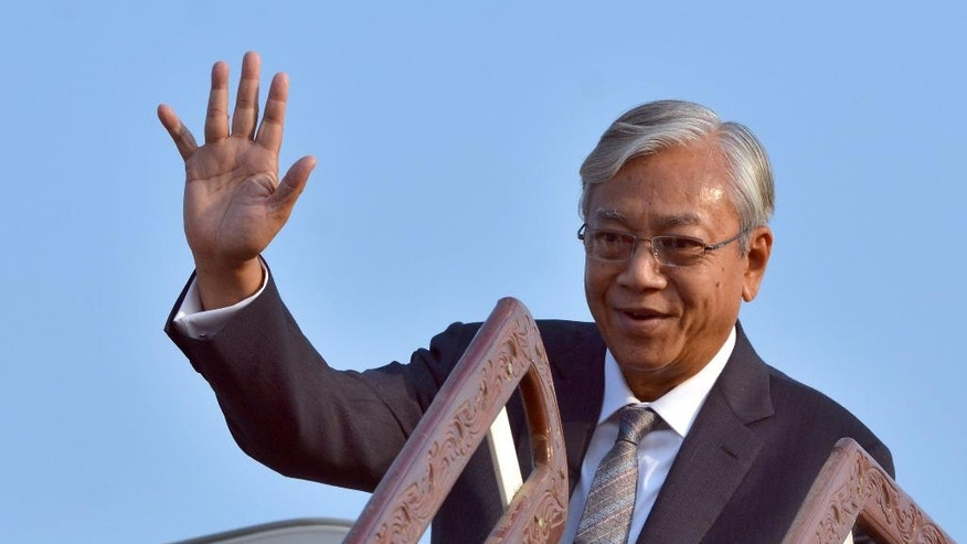 Myanmar's President Htin Kyaw waves just before taking off from capital Naypyitaw, Myanmar, Friday, May 6, 2016. Myanmar' s de facto leader Suu Kyi and President Htin Kyaw left Myanmar on a one-day official visit to Laos, their first overseas tour since taking over power in March 2016. (AP Photo/Aung Shine Oo)