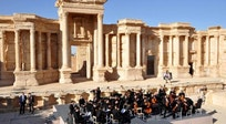 Russian orchestra performs in Palmyra as airstrike on refugee camp kills 28