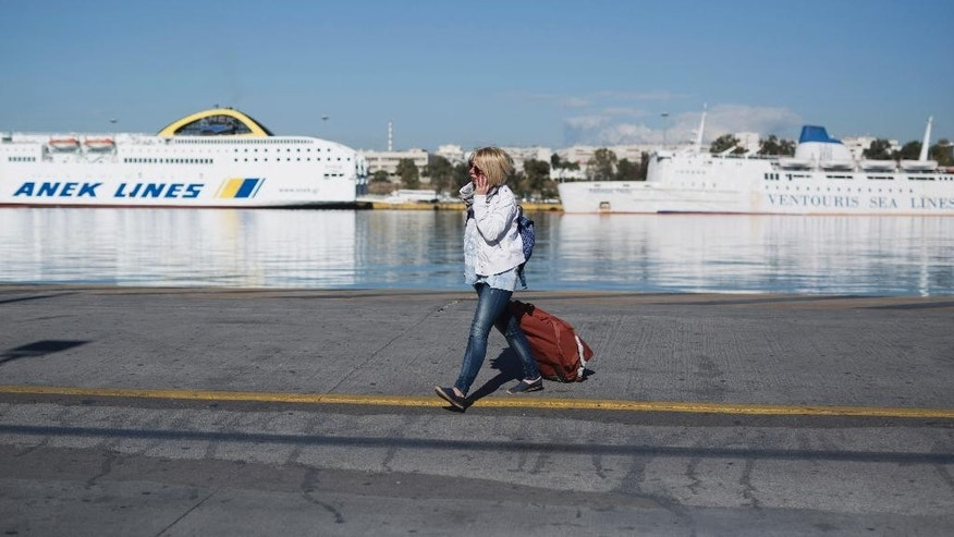 A woman carries her luggage in front of docked ferries on strike at the port of Piraeus, near Athens, on Friday, May 6, 2016. Services have ground to a halt in Greece as workers start a three-day general strike protesting new bailout austerity measures they say will further decimate incomes, in a sign of growing discontent with the left-led coalition government. (AP Photo/Petros Giannakouris)
