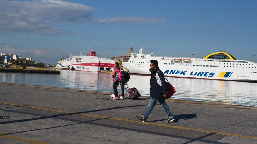 Passengers carry their belongings as they walk in front of docked ferries on strike at the port of Piraeus, near Athens, on Friday, May 6, 2016. Services have ground to a halt in Greece as workers start a three-day general strike protesting new bailout austerity measures they say will further decimate incomes, in a sign of growing discontent with the left-led coalition government. (AP Photo/Petros Giannakouris)
