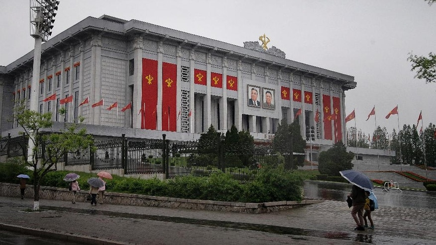 In this Thursday, May 5, 2016, photo, North Koreans walk past the April 25 House of Culture decorated in the colors and flags of their ruling party, Workers' Party, in Pyongyang, North Korea. North Korea's elite are gathered in Pyongyang ahead of their biggest political conference in decades. Foreign experts say leader Kim Jong Un will likely use the meeting, which starts Friday, to push his expansion of a nuclear arsenal over the strong objections of the U.S., the U.N. and North Korea's neighbors, including ally China. (AP Photo/Wong Maye-E)